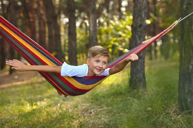 Menino bonito está sentado em uma rede.