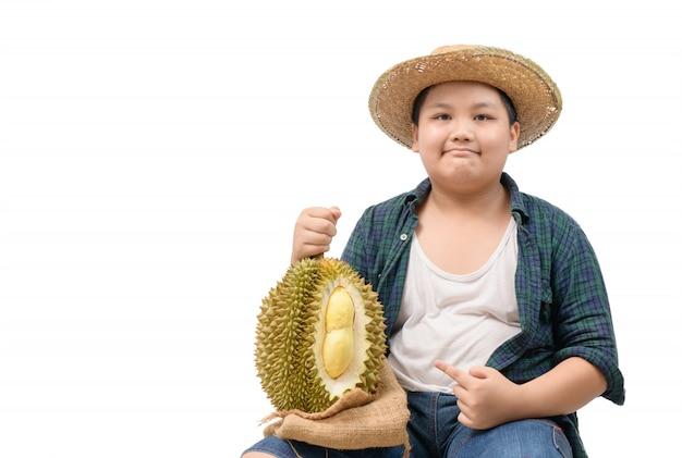 Menino bonito fazendeiro com uma fruta durian