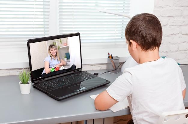 Menino bonito, fazendo aulas on-line em casa