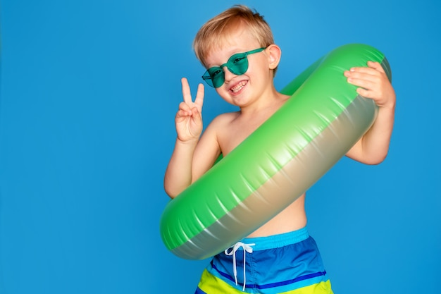 Menino bonito feliz 6-7 anos de idade em óculos de sol e com uma bóia de vida.