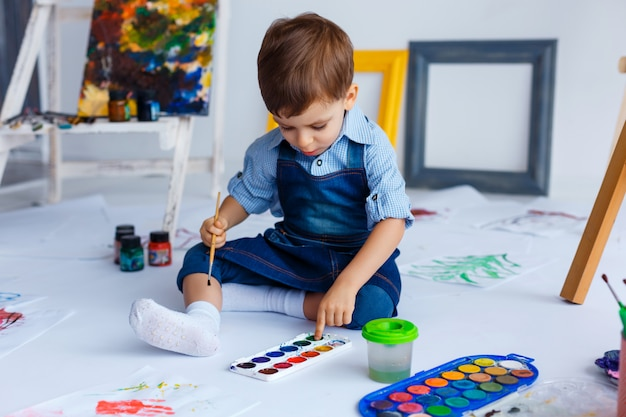 Menino bonito, feliz e branco de jeans e camisa azul desenha com tintas