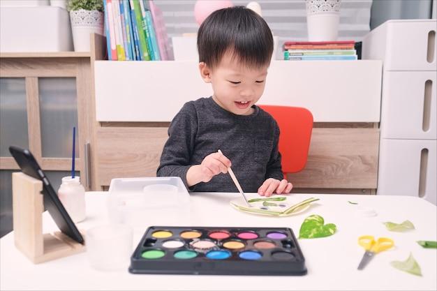 Menino bonito, feliz e sorridente, criança asiática gosta de usar cola fazendo artes em casa