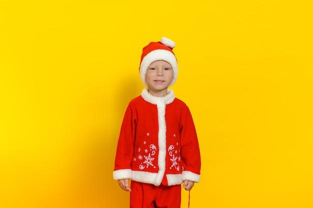 Menino bonito fica em um fundo amarelo vestido de papai noel e sorri bonito.