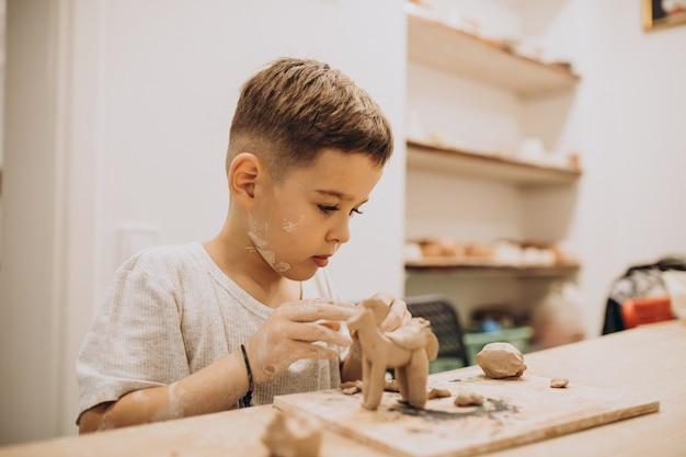 Menino bonito formando brinquedos de argila