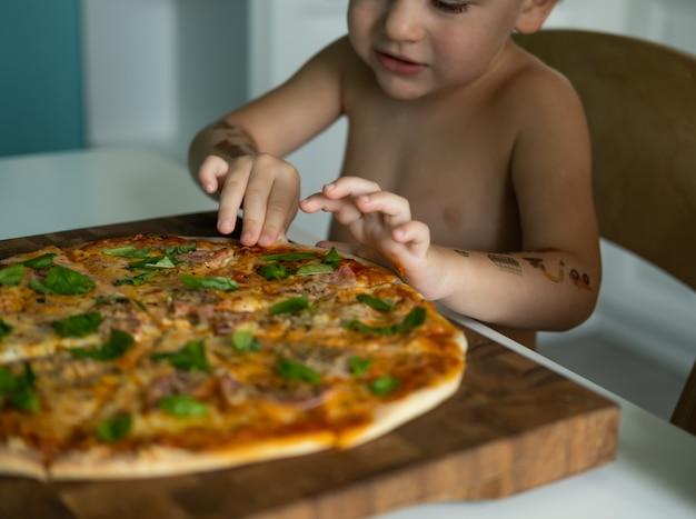 Menino bonito garoto comendo pizza caseira na cozinha em casa.