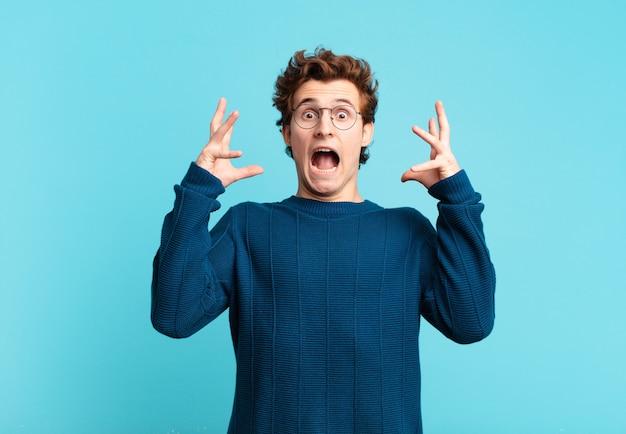 Menino bonito gritando com as mãos para o alto, sentindo-se furioso, frustrado, estressado e chateado
