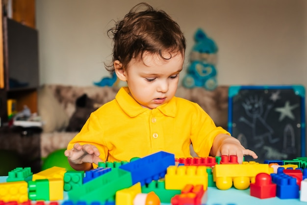 Menino bonito, jogando em casa com cubos coloridos