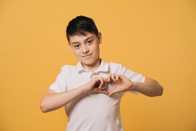 Menino bonito jovem feliz em uma camiseta branca faz formato de coração sobre o peito. emoções de pessoas sinceras.