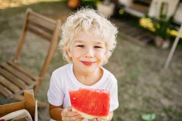 Menino bonito loiro com melancia