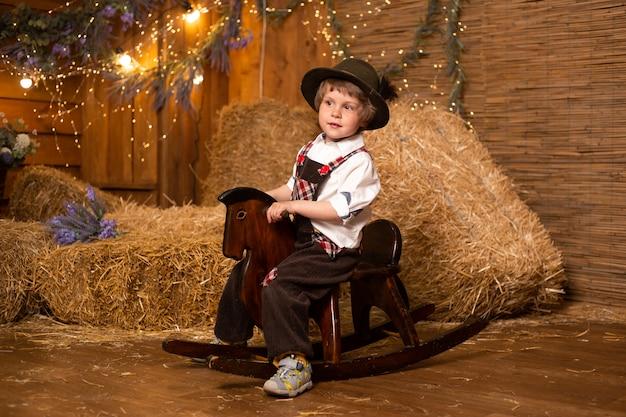 Menino bonito, montando o brinquedo tradicional de madeira do cavalo de balanço, vestindo traje retrô na fazenda com roldanas de palha.