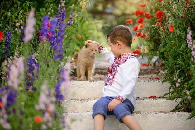 Menino bonito morena 5-6 anos de idade em um traje tradicional em um campo de papoulas no verão