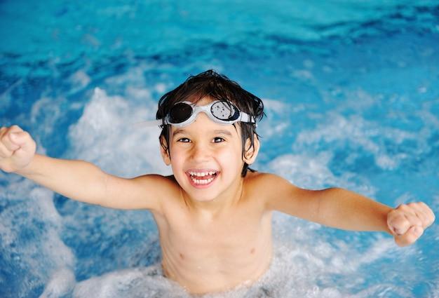 Menino bonito na água azul da piscina, horário de verão para se divertir
