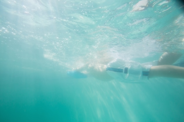 Menino bonito nadando debaixo d'água na piscina