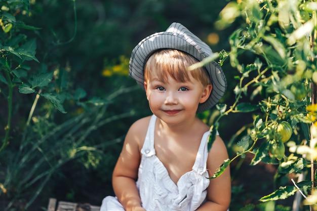 Menino bonito no chapéu e roupas casuais, sentado em torno de ang tomates olhando para a câmera