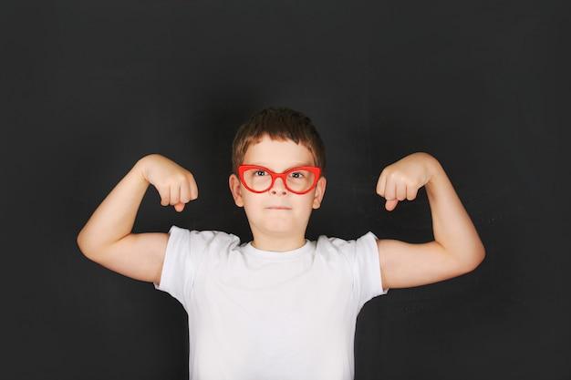 Menino bonito nos vidros cor-de-rosa que mostram seus músculos do bíceps da mão.