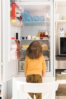 Menino bonito, olhando para a geladeira alta