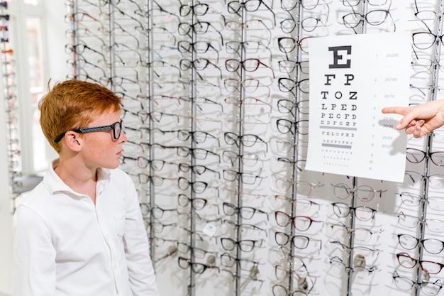 Menino bonito, olhando para o gráfico de snellen na clínica de óptica