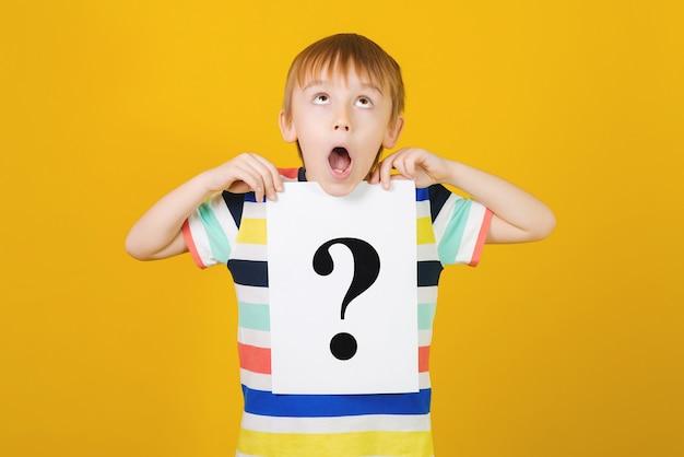 Menino bonito pensativo com ponto de interrogação e aluno mostra o ponto de interrogação.
