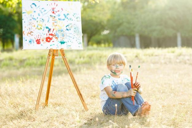 Menino bonito pequeno com escovas de pintura ao ar livre. pintor de criança. desenho de criança. garoto adorável ao ar livre no parque. pequena artista.