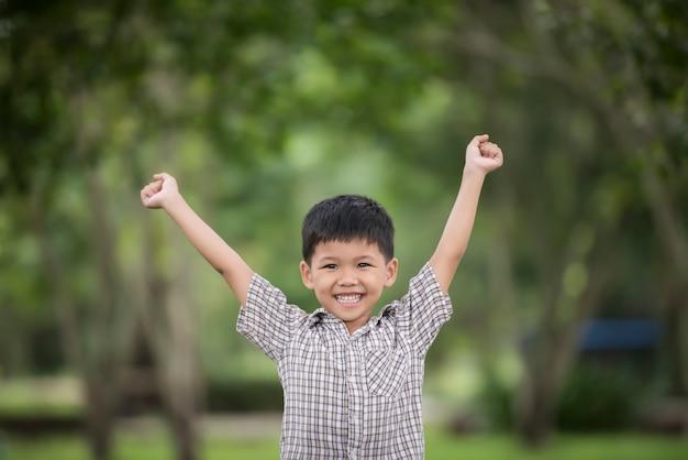 Menino bonito pequeno que aprecia levantando as mãos com natureza sobre o fundo borrado da natureza.