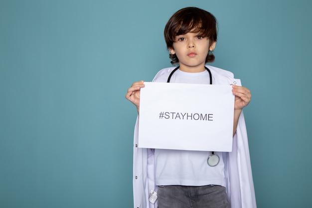 Menino bonito pouco adorável em traje médico branco e calça jeans cinza com estadia em casa hashtag contra coronavírus na mesa azul