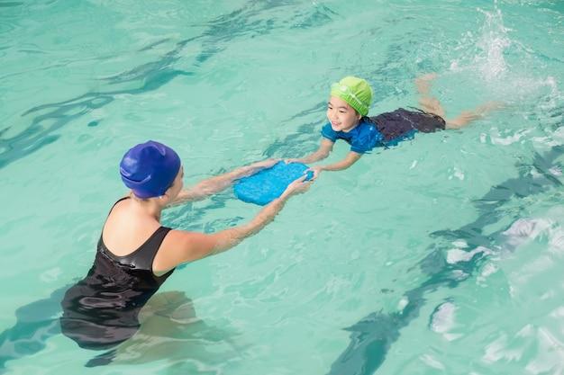 Menino bonito que aprende a nadar com treinador