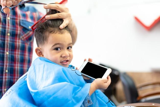 Menino bonito que obtem um corte do cabelo em uma barbearia. conceito de beleza.