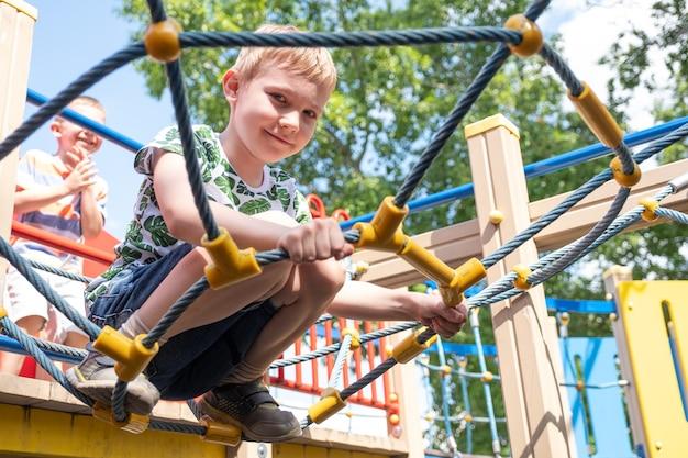 Menino bonito se divertindo e escalando no playground ao ar livre.