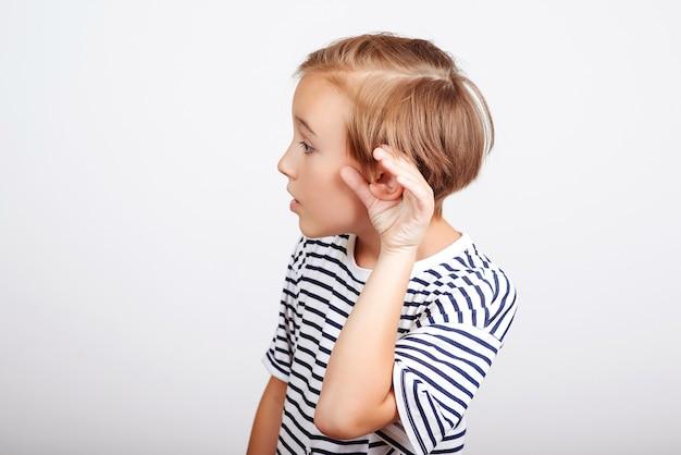 Menino bonito segura a mão perto da orelha. garoto engraçado ouve com atenção. comunicação familiar com criança. menino de escola ouvindo algo, gesto de mão na orelha.