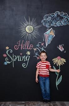 Menino bonito, segurando flor no quadro de giz preto
