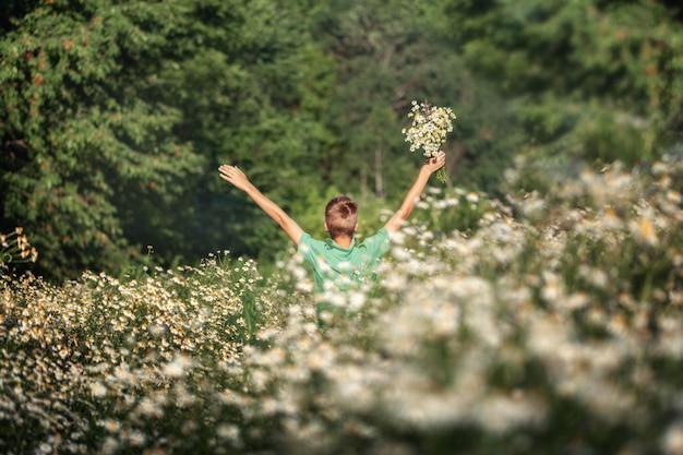 Menino bonito segurando o buquê de flores de camomila de campos em dia de verão.