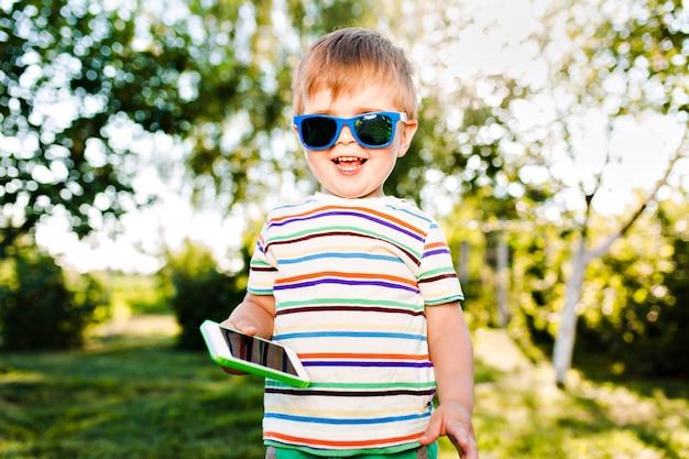 Menino bonito segurando o telefone na mão e sorrisos no jardim de verão.
