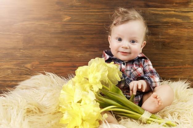 Menino bonito senta-se com tulipas amarelas na mão