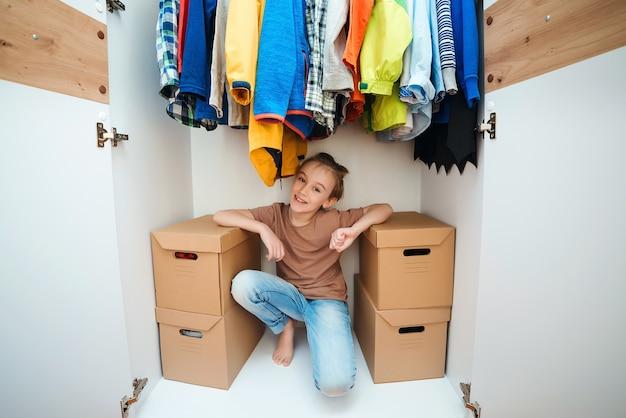 Menino bonito sentado dentro de um novo guarda-roupa moderno