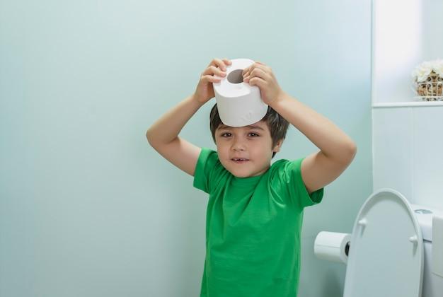 Menino bonito sentado no banheiro brincando com papel higiênico.