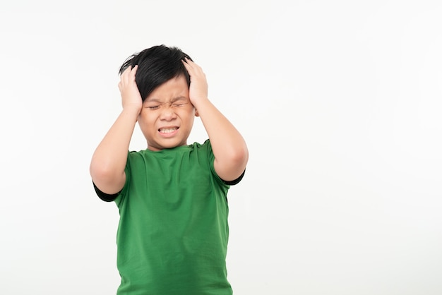 Menino bonito sofrendo de dor de cabeça em branco