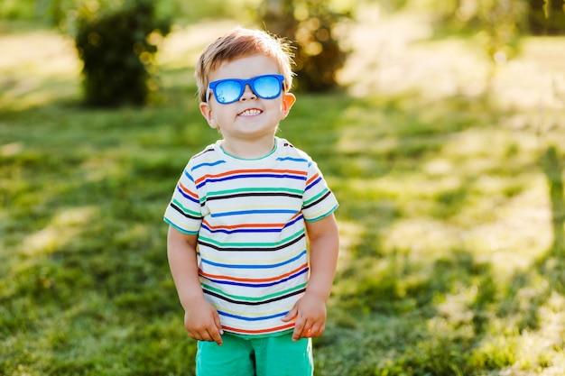 Menino bonito sorri no jardim de verão em óculos de sol brilhantes e mostra sua felicidade.