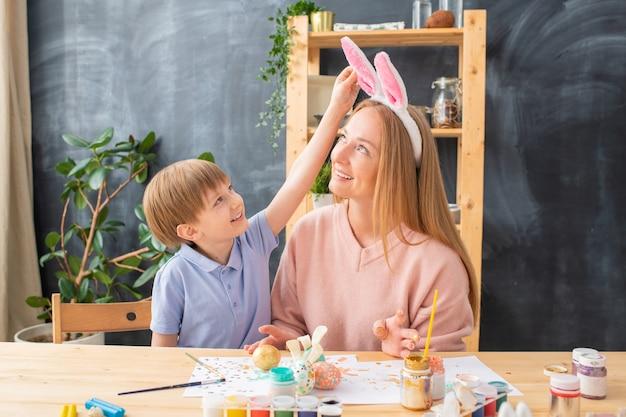 Menino bonito sorridente tocando a bandana de orelhas de coelho na cabeça da mãe enquanto elas pintam ovos na cozinha