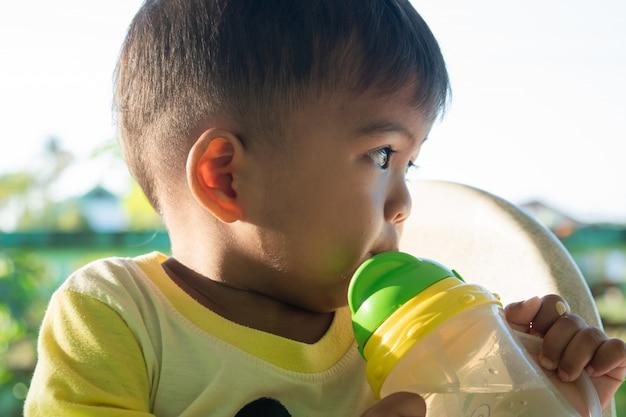 Menino bonito, sugando a água de garrafas