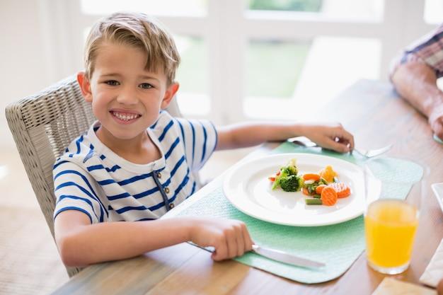 Menino bonito, tendo a refeição na mesa de jantar