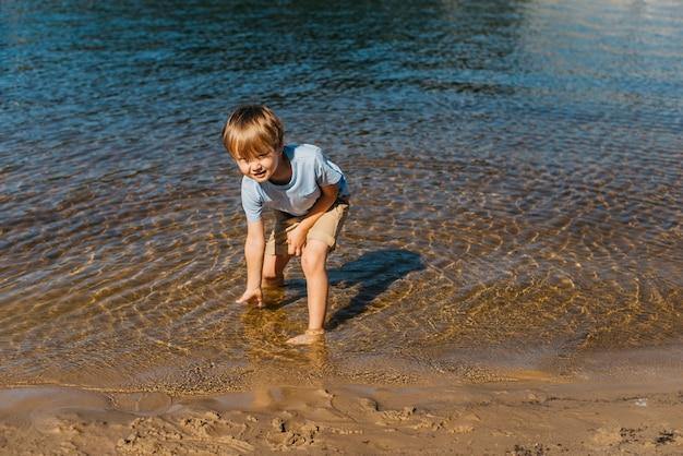 Menino bonito, tocando a água na praia