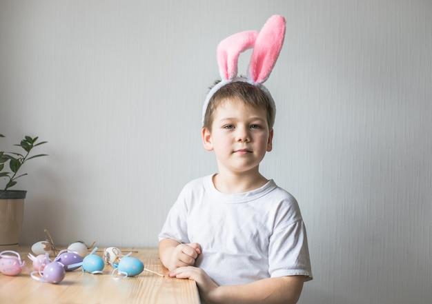 Menino bonito usando orelhas de coelho da páscoa, olha para cima.