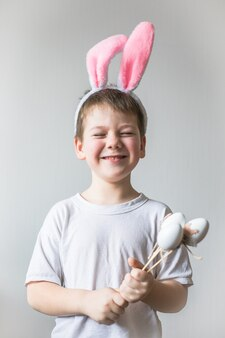 Menino bonito usando orelhas de coelho da páscoa, sorriso olha para cima.