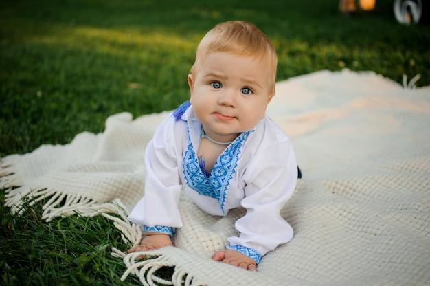 Menino bonito, vestido com a camisa bordada, deitado sobre a manta na grama verde