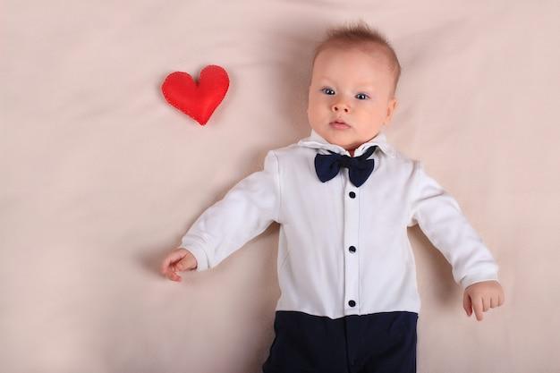 Menino bonito, vestindo smoking e gravata borboleta com coração vermelho de brinquedo como símbolo do dia das mães, com espaço de cópia