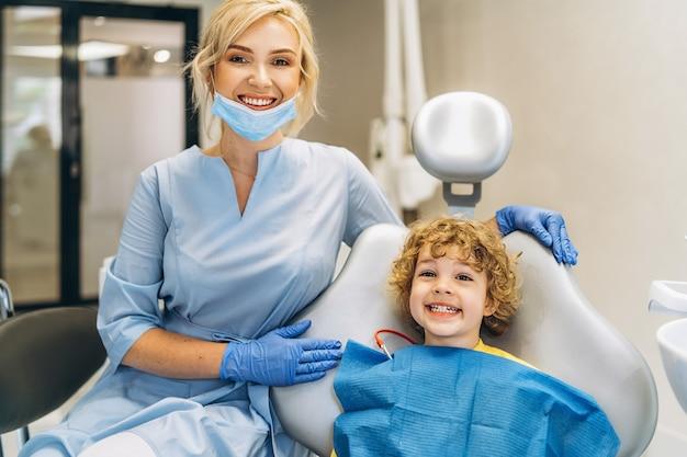 Menino bonito visitando o dentista e tendo os dentes examinados por uma dentista em um consultório odontológico