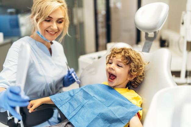 Menino bonito visitando o dentista, tendo seus dentes verificados por dentista no consultório odontológico.