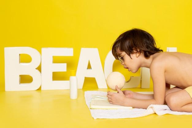Menino bonito vista frontal, juntamente com a palavra praia amarelo