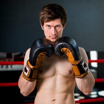 Menino boxer posando no ginásio