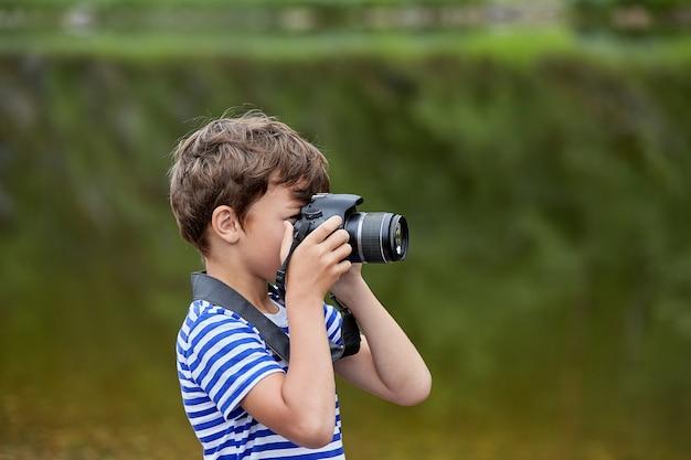 Menino branco de cerca de 8 anos de idade está parado perto do rio e tirando fotos com a câmera.